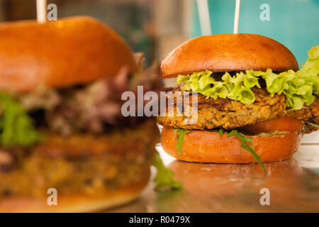 Two tasty burgers in front of a colorful background - Stock Photo