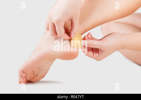 Closeup of woman's heel with blister plaster on. Band-aid on the blister on the leg. First aid - Stock Photo