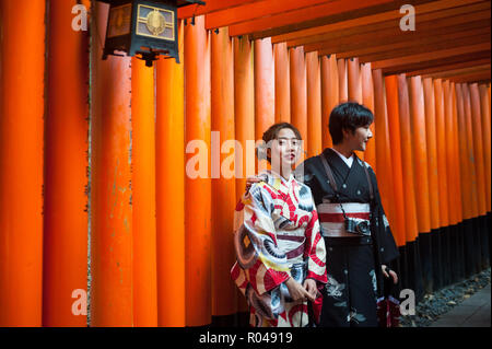 Kyoto, Japan, Two Japanese women stand in a Torii path to the Fushimi Inari-Taisha - Stock Photo