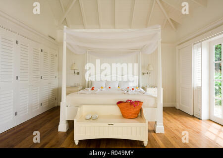 Bedroom with white four poster bed - Stock Photo