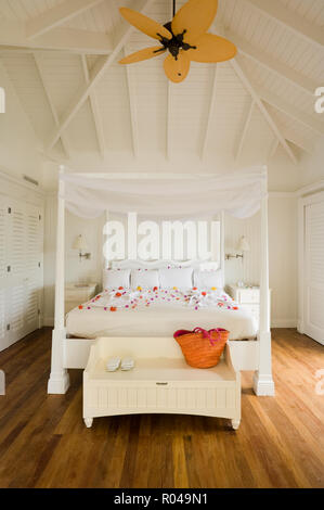 Bedroom with four poster bed and ceiling fan - Stock Photo