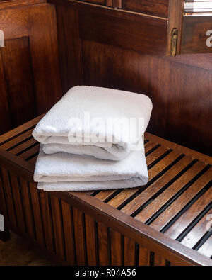 Towels on wooden bench - Stock Photo