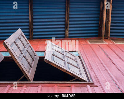 Wooden window is opened on the second floor of the countryside house,view from the ground to the top of the house. - Stock Photo