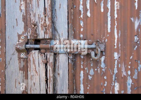 A rusty painted slide bolt secured with a Lockwood padlock and a embedded key lock in an old wooden door with peeling paint - Stock Photo