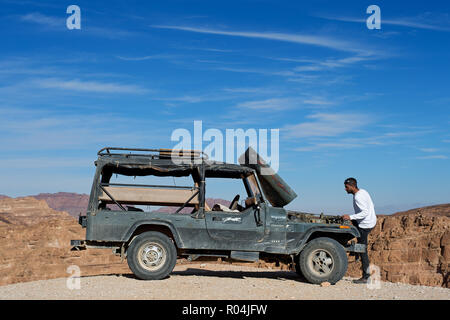 Man trying to repair his truck in Coloured Canyon. Nuweiba. Egypt - Stock Photo