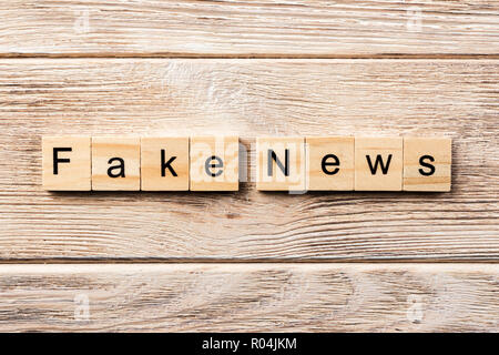 fake news word written on wood block. fake news text on table, concept. - Stock Photo