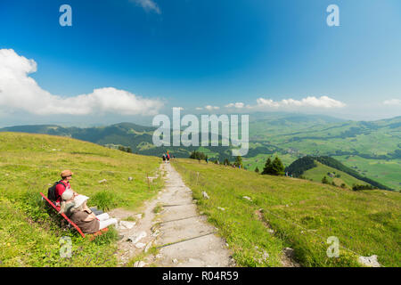 People on bench in the green valley of Ebenalp looking towards Appenzell and Schwende, Appenzell Innerrhoden, Switzerland, Europe - Stock Photo
