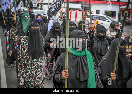 Female protesters seen holding flags during the protest. Muslims throughout Indonesia held protests against the burning of the Tauhid Islamic flag in front of the Lhokseumawe Islamic Center Mosque. Violent protests by Indonesian Muslims after the circulation of videos of burning the Tauhid Islamic flag (La Illah ha illallah Muhammaddurrasulullah) by a number of BANSER (Multipurpose Ansor Barisan) members. - Stock Photo