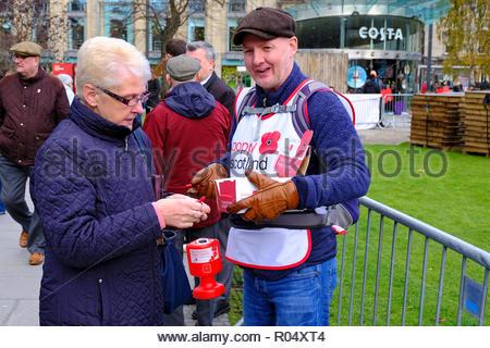 Edinburgh, United Kingdom. 1st November, 2018.  Edinburgh Poppy Day hosted by PoppyScotland in St Andrew Square.   Poppy Scotland volunteer selling poppies. Credit: Craig Brown/Alamy Live News. - Stock Photo