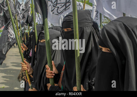 Lhokseumawe, Aceh, Indonesia. 1st Nov, 2018. Female protesters seen holding flags during the protest.Muslims throughout Indonesia held protests against the burning of the Tauhid Islamic flag in front of the Lhokseumawe Islamic Center Mosque.Violent protests by Indonesian Muslims after the circulation of videos of burning the Tauhid Islamic flag (La Illah ha illallah Muhammaddurrasulullah) by a number of BANSER (Multipurpose Ansor Barisan) members. Credit: Maskur Has/SOPA Images/ZUMA Wire/Alamy Live News - Stock Photo