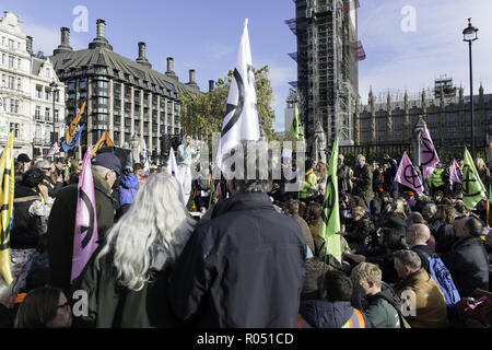 London, Greater London, UK. 31st Oct, 2018. Hundreds of environmental activist were seen blocking the road outside Parliament during the protest.The newly formed Extinction Rebellion group, concerned about climate change, calls for a peaceful mass civil disobedience to highlight politicians' lack of commitment and action regarding environmental issues. Activists gathered at the Parliament Square and blocked the road for two hour. The protest included speakers such as Greta Thunberg, Caroline Lucas, and George Monbiot. According to Extinction Rebellion 15 people were arrested - Stock Photo
