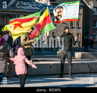 Holyrood, Edinburgh, Scotland, United Kingdom, 2nd November 2018. Kurdish protestors and families stand outside the Scottish Parliament building waving flags supporting the release of Kurdish nationalist Abdullah Öcalan and in protest at the treatment by the Turkish state of Kobane, a city in the Aleppo Governorate in northern Syria - Stock Photo