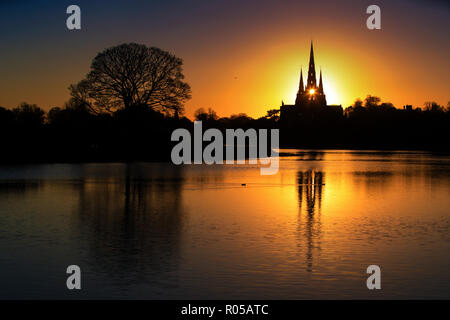02/11/18  Ahead of a cold night the setting sun shines through the central spire of Lichfield Cathedral, and is reflected in Stowe Pool.  The Staffordshire medieval cathedral  is the only English cathedral with three spires. The three spires are often referred to as 'the Ladies of the Vale'. - Stock Photo