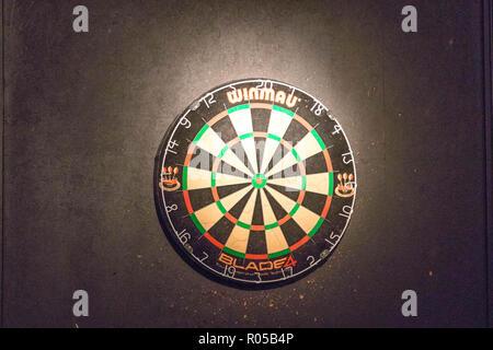 Darts board in a pub game - Stock Photo