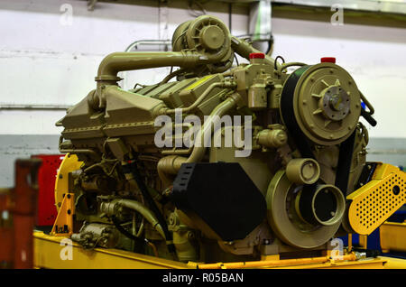 Large diesel engine with a huge turbine in the warehouse of finished products factory for the production of large mining trucks - Stock Photo