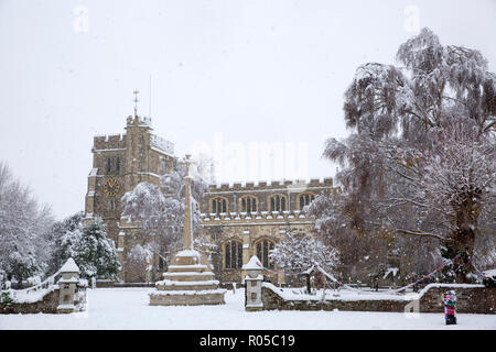 War memorial and Parish Church of St Peter and St Paul, in the market town of Tring, Hertfordshire, England, covered in snow during winter blizzard - Stock Photo