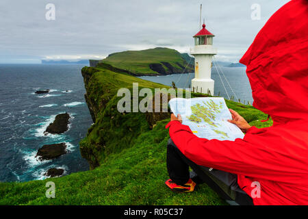 Hiker on cliffs looks at the map next to lighthouse, Mykines island, Faroe Islands, Denmark - Stock Photo