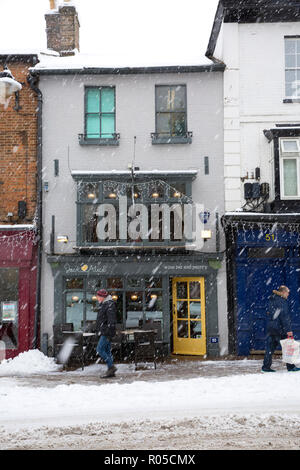 Shops on the High Street in the market town of Tring, Hertfordshire, England, covered in snow during winter blizzard - Stock Photo