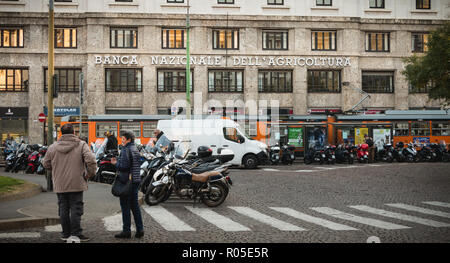 Milan, Italy - November 3, 2018: Elderly couple chatting on a paved road in front of the National Bank of Agriculture on a fall day - Stock Photo