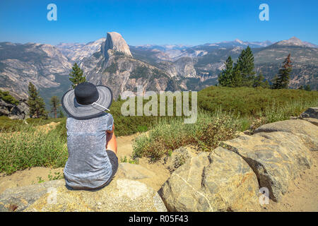 Traveler woman looking panorama at Glacier Point in Yosemite National Park, California, USA. The view from Glacier Point: Half Dome, Liberty Cap, Yosemite Valley and Nevada Fall. Summer travel concept - Stock Photo