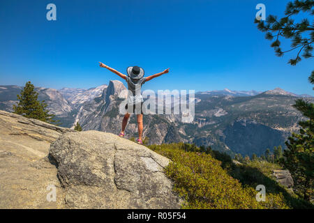 Travelling enthusiast woman happy for the Glacier Point aerial view in Yosemite National Park, California, US. Glacier Point panorama: Half Dome, Liberty Cap, Yosemite Valley, Vernal Fall, Nevada Fall - Stock Photo