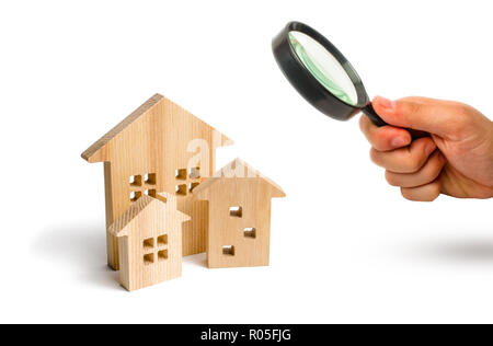 Magnifying glass is looking at the City of wooden houses on a white background. The concept of urban planning, infrastructure projects. Buying and sel - Stock Photo
