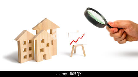 Magnifying glass is looking at the Wooden houses stand with red arrow up. Growing demand for housing and real estate. The growth of the city and its p - Stock Photo