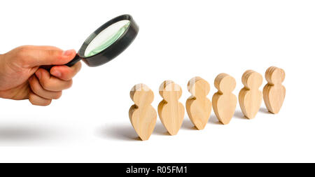 Magnifying glass is looking at the People stand in a formation on a white background. Discipline and order, submission. In anticipation of an order. P - Stock Photo