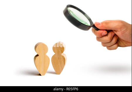 Magnifying glass is looking at the Two people stand together and talk. Three wooden figures of people conduct a conversation on a blue background. Com - Stock Photo