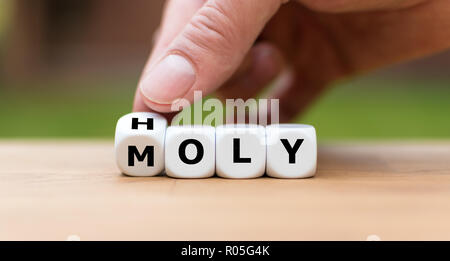 Hand is turning a dice and changes the word 'holy' to 'moly' - Stock Photo