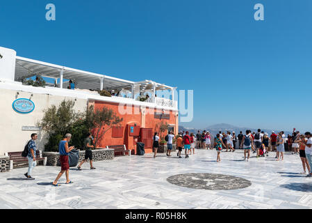 SANTORINI, GREECE - AUGUST 2018: Tourists are visiting central square at Oia town. - Stock Photo