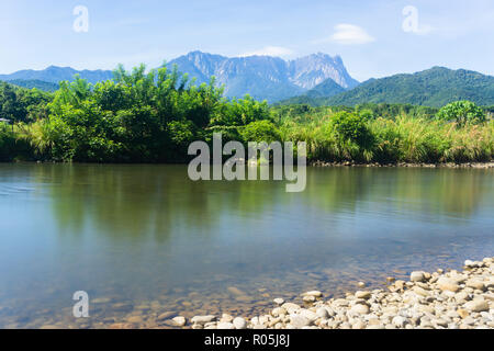 Landscape of rural Sabah Malaysia Borneo with river flowing and the Mount Kinabalu at far background during sunny blue sky. - Stock Photo