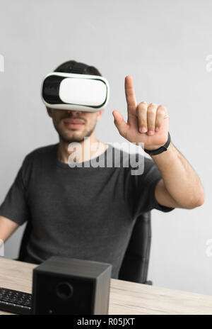 Young man wearing virtual reality goggles headset and sitting in the office against computer. Connection, technology, new generation. Man trying to touch objects or control VR with a hand. - Stock Photo