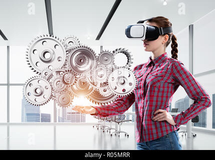 Girl in casual wearing VR glasses and experiencing virtual reality. Mixed media - Stock Photo