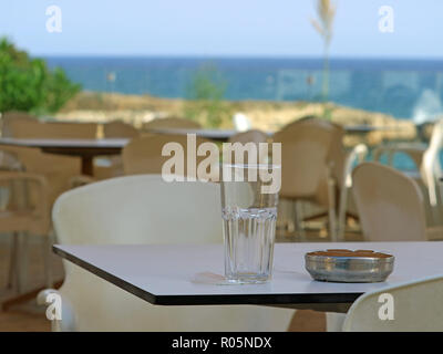 emty glass and ashtray on table in a restaurant near the beach - Stock Photo