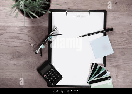 top view.clipboard with blank sheet, pen, glasses and calculator - Stock Photo