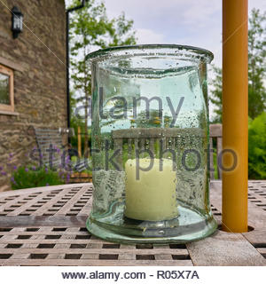 a large white unlit candle inside a glass jar covered with rain drops on a wooden patio outside in a british uk garden - Stock Photo