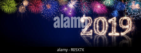 colorful fireworks and bright sparkler pyrotechnic number 2019 happy new year sylvester concept on black blue panorama background - Stock Photo