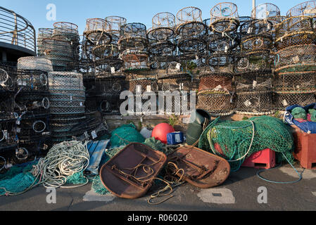 Fishing nets, lobster pots and other fishing equipment on the quay in the port of Brixham, Devon,UK - Stock Photo