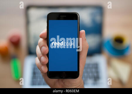 A man looks at his iPhone which displays the Reed logo, while sat at his computer desk (Editorial use only). - Stock Photo