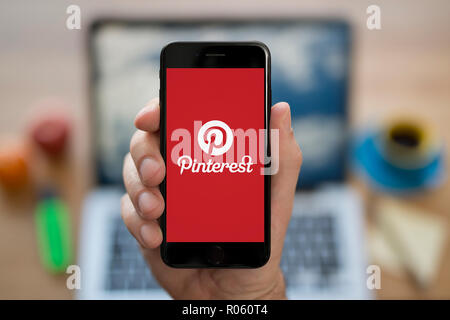 A man looks at his iPhone which displays the Pinterest logo, while sat at his computer desk (Editorial use only). - Stock Photo