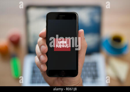 A man looks at his iPhone which displays the BBC News logo, while sat at his computer desk (Editorial use only). - Stock Photo