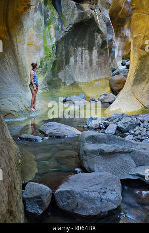 Adult caucasian female standing by the stream in the Tunnel. Drakensberg Ukhahlamba National Park, Kwazulu Natal Province, South Africa - Stock Photo