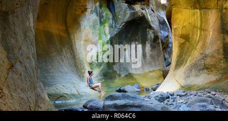 Adult caucasian female surveying the Tunnel. Drakensberg Ukhahlamba National Park, Kwazulu Natal Province, South Africa - Stock Photo