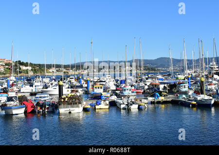 Sanxenxo, Spain. October 2018. Boats in a pier. Small coastal village. Sunny day, blue sky, blue water with reflections. Fishing and sailing industry. - Stock Photo