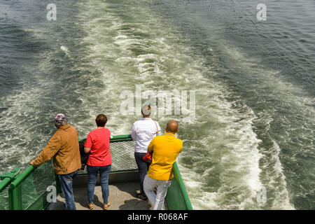 EN ROUTE SEATTLE TO BREMERTON - JUNE 2018: People standing on a platform on the back of a passenger ferry from Seattle to Bremerton. - Stock Photo