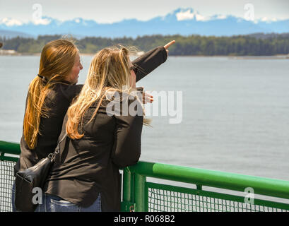 EN ROUTE SEATTLE TO BREMERTON - JUNE 2018: Person pointing out something of interest to her friend on a passenger ferry from Seattle to Bremerton. - Stock Photo