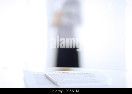 Contract with a pen and blurred business people on the background, close-up - Stock Photo