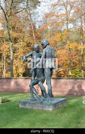 A bronze statue in Autumn in the War Cemetery in Reimsbach depicts two men carrying a deadly wounded victim as a symbol of the helplessness of man. - Stock Photo
