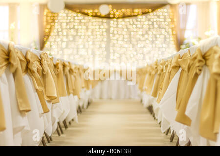 Wedding table that decorated with flower arrangements and candles. Golden lights and white chairs, beautiful celebration of wedding concept - Stock Photo